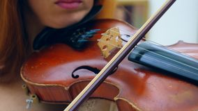 Fiddler holds a violin on a shoulder, playing it in a museum. 4K stock footage
