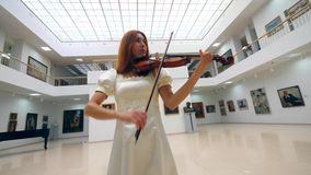 A fiddler plays instrument, standing in a room with pictures on walls. 4K stock video