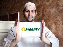 Fidelity Investments company logo. Logo of Fidelity Investments company on samsung tablet holded by arab muslim man. Fidelity is a multinational financial Royalty Free Stock Image