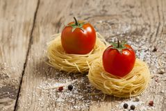 Fidellini dried pasta and fresh organic tomatoes on a wooden tab stock photos