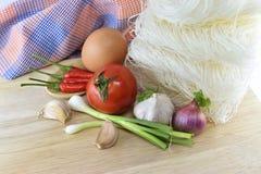 Fideos, chile, cebolla, huevo, ajo y tomate en vagos de madera Fotografía de archivo libre de regalías