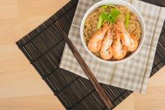 Fideos cocidos con el camarón en el plato de madera Fotos de archivo