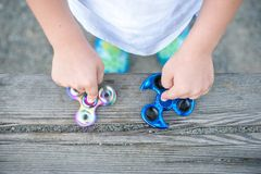 Fidget μπλε και ουράνιων τόξων εκμετάλλευσης αγοριών κλώστες στα χέρια του, άποψη Στοκ Εικόνες
