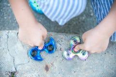 Fidget μπλε και ουράνιων τόξων εκμετάλλευσης αγοριών οι κλώστες στα χέρια του, βλέπουν άνωθεν την περιστροφή και των δύο συσκευών Στοκ φωτογραφία με δικαίωμα ελεύθερης χρήσης