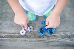 Fidget μπλε και ουράνιων τόξων εκμετάλλευσης αγοριών οι κλώστες στα χέρια του, βλέπουν άνωθεν την περιστροφή και των δύο συσκευών Στοκ Φωτογραφίες