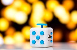 Fidget cube anti stress toy. Detail of finger play toy used for relax. Gadget placed on colorful bokeh background. Fidget cube antis stress toy. Detail of finger royalty free stock photos