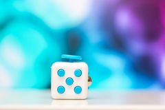 Fidget cube anti stress toy. Detail of finger play toy used for relax. Gadget placed on colorful bokeh background. Fidget cube antis stress toy. Detail of finger royalty free stock photography