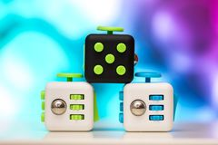 Fidget cube anti stress toy. Detail of finger play toy used for relax. Gadget placed on colorful bokeh background. Fidget cube antis stress toy. Detail of finger stock photos