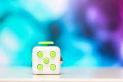 Fidget cube anti stress toy. Detail of finger play toy used for relax. Gadget placed on colorful bokeh background. Fidget cube antis stress toy. Detail of finger royalty free stock photo