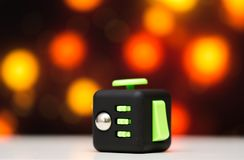 Fidget cube anti stress toy. Detail of finger play toy used for relax. Gadget placed on colorful bokeh background. Fidget cube antis stress toy. Detail of finger stock photography