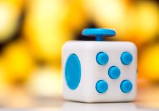 Fidget cube anti stress toy. Detail of finger play toy used for relax. Gadget placed on colorful bokeh background. Fidget cube antis stress toy. Detail of finger stock image