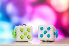Fidget cube anti stress toy. Detail of finger play toy used for relax. Gadget placed on colorful bokeh background. Fidget cube antis stress toy. Detail of finger royalty free stock images