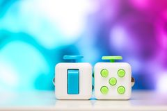 Fidget cube anti stress toy. Detail of finger play toy used for relax. Gadget placed on colorful bokeh background. Fidget cube antis stress toy. Detail of finger royalty free stock image