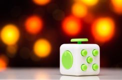 Fidget cube anti stress toy. Detail of finger play toy used for relax. Gadget placed on colorful bokeh background. Fidget cube antis stress toy. Detail of finger stock images