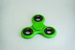 Fidget finger spinner stress, anxiety relief toy. A fidget spinner is a type of stress-relieving toy. A basic fidget spinner consists of a bearing in the center royalty free stock images