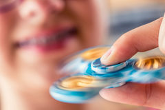 Fidget Spinner. Cute young girl playing with fidget spinner Stock Photography