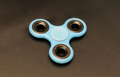 Fidget spinner on dark background. Blue fidget spinner on dark background Stock Photos
