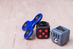 Fidget spinner and fidget cube, the latest stress relieving craze. On table top royalty free stock photos