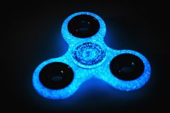 Fidget Spinner glows in the dark, selective focus royalty free stock photography