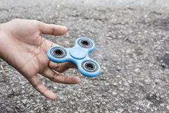 Fidget Spinner. Kid play with fidget spinner stress relieving toy Stock Photo