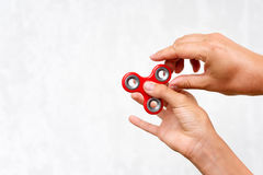 Fidget spinner. Red hand spinner, boys playing with fidgeting hand toy. Stress relief. Anti stress and relaxation adhd attention f. Ad boy concept. Free space Stock Photography