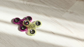 Fidget spinners pink and green stress relieving toys closeup in sunlight royalty free stock images