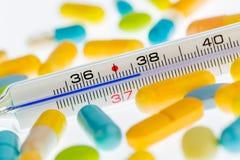 Fieberthermometer und Pillen Lizenzfreie Stockbilder