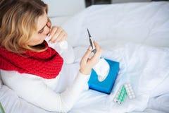 Fiebre y fr?o Retrato de la gripe cogida mujer hermosa, teniendo dolor de cabeza y temperatura alta Primer de la muchacha enferma imagenes de archivo