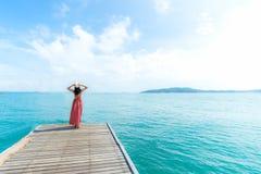 field вал Усмехаясь женщины ослабляют и нося красная мода стоя на деревянном мосте над морем, предпосылка платья голубого неба стоковые фотографии rf
