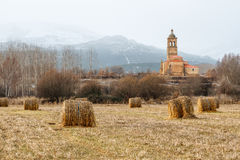Field with alpacas of straw and Church of the Christ. Tabuyo del Monte, Leon, Spain. Royalty Free Stock Photo