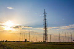 Field with antennas. A field in sunset light and tall radio antennas in the distance royalty free stock image