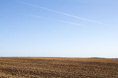 Field on a background of the sky. Sunny spring morning. Freshly plowed field . Blue sky with white stripes obloka over the field . Somewhere in the distance edge Stock Photos