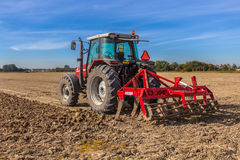 Field being ploughed. By tractor with Plough under Blue Sky. Farming scene in the Netherlands Royalty Free Stock Photo
