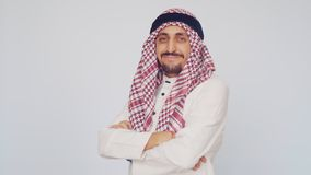 The field of business and trade. A man with a beard and national dress smiling. Arab in a modern office folded his hands stock video