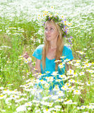Field of camomiles and the young woman with a wreath from flowers on the head Royalty Free Stock Photos