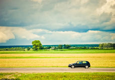Field and car on a road Royalty Free Stock Photos