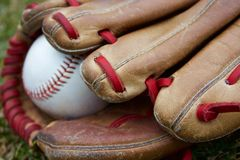 In the field. Close up of baseball and glove with unique red lacing Stock Images