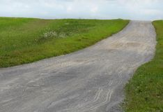 Field and country road. Grass field and country road Royalty Free Stock Images