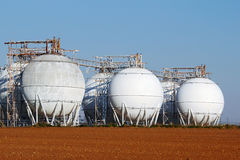 Field of crude oil tanks on agriculture field Royalty Free Stock Photo