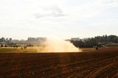 Field cultivated during watering. Day royalty free stock photo