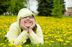Field of Dandelions Portrait. A young girl lying in a field of dandelions Stock Photography