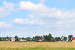 Field with dry grass and houses of village Stock Image