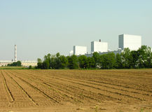 Field and factory. A rural field infront of an industrial factory Royalty Free Stock Image