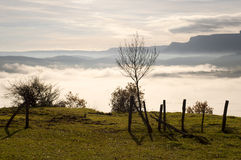 Field fence with a gate, with mountains in the background, and fog in the valley Royalty Free Stock Photos