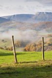 Field fence, with green grass, mountains in the background, and fog Royalty Free Stock Photos