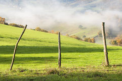 Field fence, with green grass, mountains in the background, and fog Royalty Free Stock Images