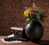 Field flowers, old box, gun and dollars Stock Image