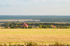 Field, forest and homes in the distance Stock Photos