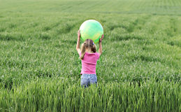 Field of fun 2. A little girl playing with her ball in a colorful field of wheat grass stock images