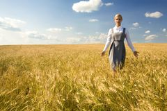 In the field of gold. Smart female walking in wheat field against cloudy sky Royalty Free Stock Image